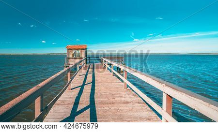 Old Wooden Pier For Fishing, Small House Shed And Beautiful Lake Or River In Background. Picturesque