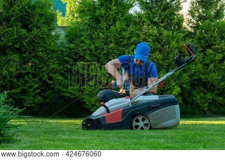 A Professional Repairman Repairs A Lawn Mower, A Man Repairs A Mower In His Backyard