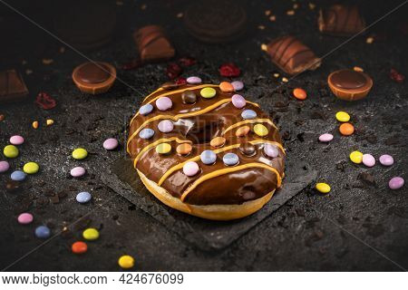 Fast Sweet Food Concept, Sweet Chocolate Glazed Donut Decorated With Firecracker Candy