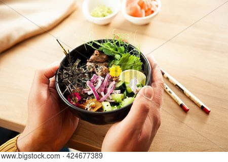 A Man Holds A Poke Salad With Beef In A Bowl In His Hands. Ingredients Beef, Nameko Mushrooms, Cherr