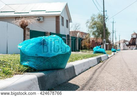A Plastic Garbage Bag With Waste Lying On The Sidewalk Of A Suburb. Close Up. Concept Of Municipal C
