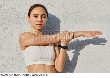 Beautiful Fitness Model Girl Wearing Sport Clothes Posing Against Gray Wall Outdoor, Warming Up Befo
