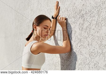 Outdoor Portrait Of Young Adult Dreamy Pensive Standing Leaning On Grey Wall, Being Tired After Spor
