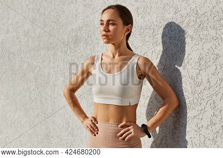 Portrait Of Confident Serious Female With Dark Hair Wearing White Top, Looking Away With Pensive Exp