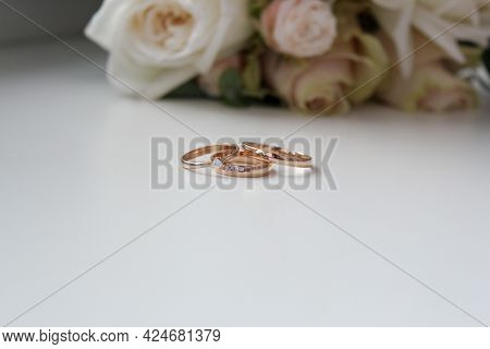Gold Wedding Rings And Bouquet With Beautiful Roses. High Quality Photo