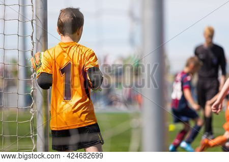 Young Boy Soccer Goalie Standing In A Goal In Orange Football Uniform. Child Kicking Football Tourna
