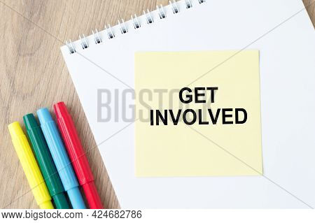 Get Involved On A Yellow Sticker On A White Notepad On A Wooden Background. Motivational Concept Ima