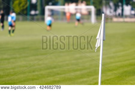 Football Corner White Flag. Soccer Turf Pitch In A Blurred Background. Players Kicking Soccer Game