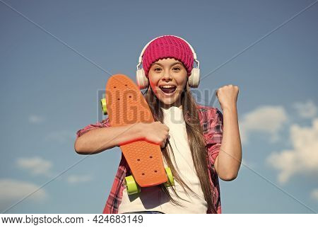 Happy Girl Make Winner Gesture Holding Skateboard And Listening To Music In Modern Headphones Sunny