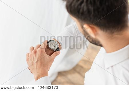 High Angle View Of Blurred Businessman Wearing Wristwatch At Home