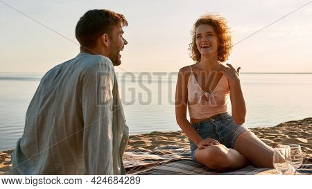 Laughing Young Caucasian Couple Sitting On Sand At Sunny Beach In Summer And Talking, Widescreen. Ro