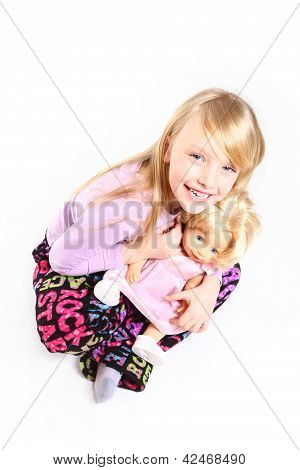 Portrait Of Cute Smiling Little Girl With A Doll Sitting Isolated On White Background