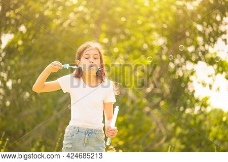 Cute Girl Is Blowing A Soap Bubbles. Girl Teenager Blowing Soap Bubbles Outdoors. Happiness, Summer