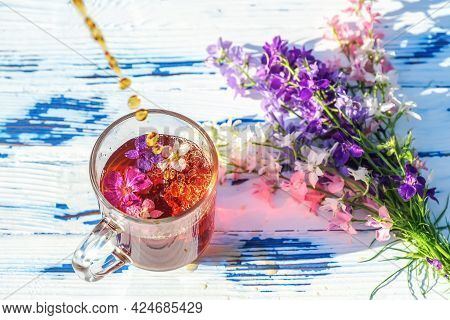 Transparent Glass Cup Of Tea With Wildflowers And A Bouquet On A Wooden Table Close-up. Summer Lifes