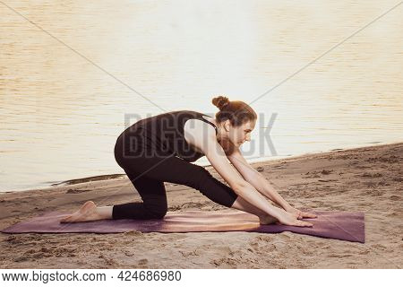 A Woman In Black Sportswear Is Doing Stretching, Yoga Or Fitness On The River Bank At Sunset. Stretc
