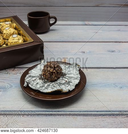 On The Saucer Lies A Chocolate-nut Candy In An Unfolded Foil Wrapper. Next To It Is A Box Of Chocola