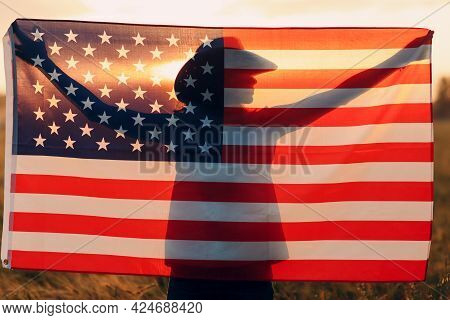 Woman Sunset Silhouette In The Agricultural Field Behind American Flag