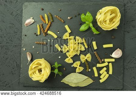 A Set Of Pasta And Noodles With Spices On A Stone Cutting Board. Raw Pasta And Spices As A Backgroun