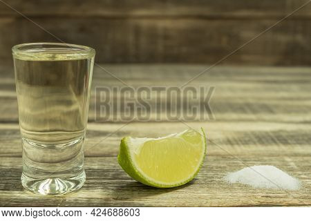 Tequila With Lime And Salt On A Vintage Wood Background. A Slice Of Lemon Close-up And A Glass Of Te