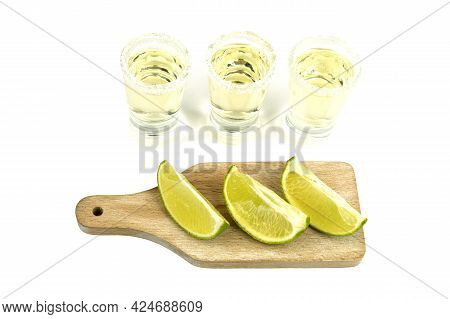 Shot Glass With Tequila And Lime On A White Background. A Slice Of Lemon Close-up On A Stone Cutting