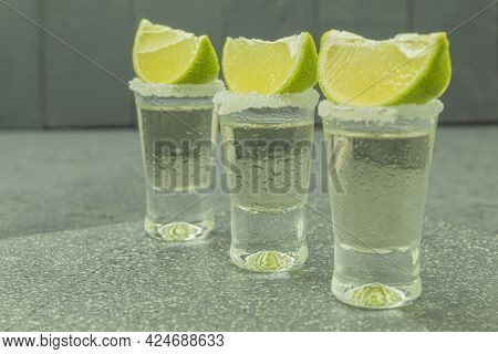 Three Glasses With Tequila And Lime On A Stone Board. Glasses With Tequila On The Table. Background