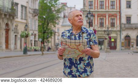 Elderly Mature Stylish Tourist Man Walking Along Street, Looking For Way Using Paper Map In Old Town
