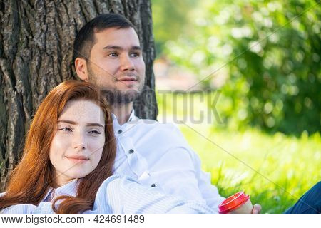 Young Couple Relaxing With Coffee Under Tree In Park On Sunny Day. Happy Couple In Love Spend Time O