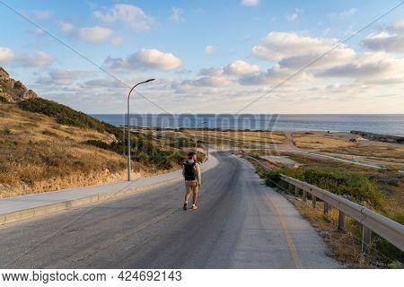 Male Tourist Hikers On An Asphalt Mountain Road Overlooking The Sea In Cyprus Near Agios Georgios Pe