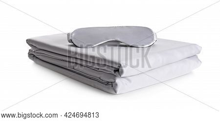 Stack Of Clean Silky Bed Linen And Sleeping Mask Isolated On White