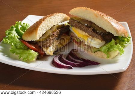 Large Delicious Hamburger Cut With Fried Patty, Fried Egg, Pickles, Tomato And Lettuce On A White Pl