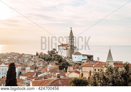 A Panoramic Of Old Town Piran, Slovenia At Sunset. View Over The Tiled Roofs Of Piran And The Adriat