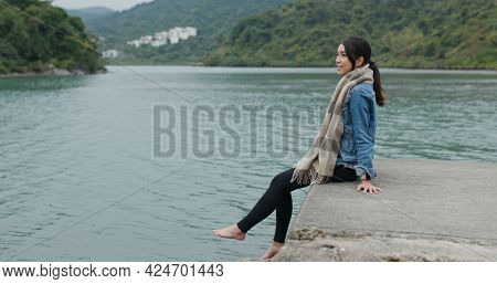 Woman sits on the pier swinging feet
