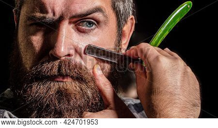 Vintage Straight Razor. Handsome Bearded Hairdresser In Stylish Wear Is Holding A Straight Razor Whi