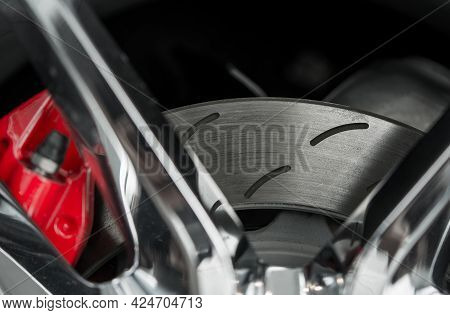 Automotive Industry Theme. Modern Car Brake Disc With Red Caliper Close Up Photo. Performance Vehicl