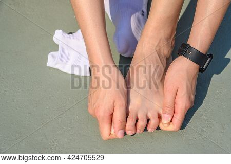 Cropped View Of Runner Woman Suffering From Foot Injury And She Trying To Do Foot Massage By Herself