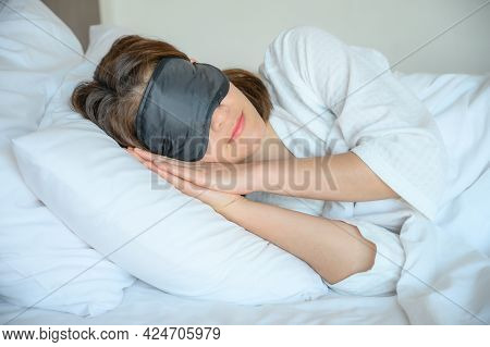 Portrait Of Young Beautiful Woman Wearing Sleep Mask During Sleeping On The Bed. A Sleep Mask Can Bl