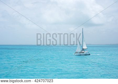A Luxury Catamaran With Some Tourists Sailing In The Ocean Of The Mexican Caribbean