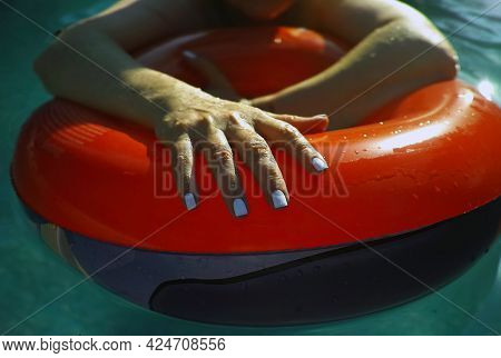 Female Hands With Manicure Nails On Inflatable Swimming Circle