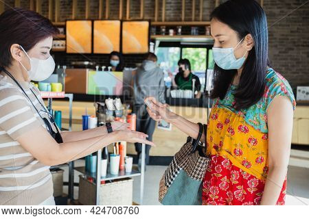 Two Female In Face Mask Friends Spraying Their Hands With Antiseptic Spray In Cafe