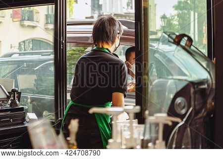 Coffee Shop Staff With Protective Mask Serving Coffee To Customer At Drive Thru