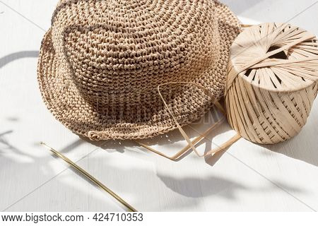 The Process Of Knitting A Raffia Hat, A Skein Of Yarn, A Hook On A Wooden Background