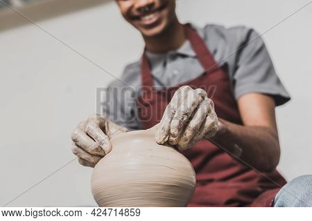 Partial View Of Young African American Man In Apron Sculpting Clay Pot In Pottery