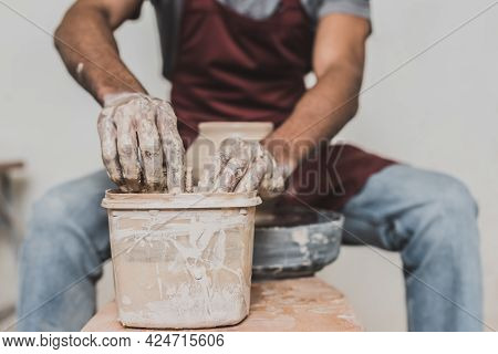 Partial View Of Young African American Man Washing Sponge In Plastic Box While Sculpting Pot On Whee