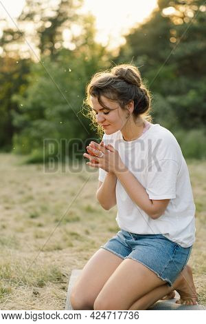 Woman Closed Her Eyes, Praying In A Field During Beautiful Sunset. Hands Folded In Prayer Concept Fo
