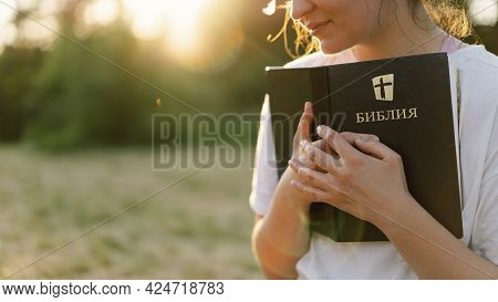 Christian Woman Holds Bible In Her Hands. Reading The Holy Bible In A Field During Beautiful Sunset.