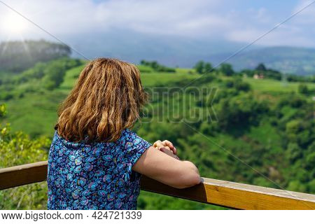 Woman Contemplating The Green Valley From A Viewpoint With Flashes Of The Sun On The Horizon. Santan