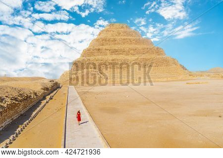 A Young Girl In A Red Dress Walking In The Stepped Pyramid Of Djoser, Saqqara. Egypt. The Most Impor