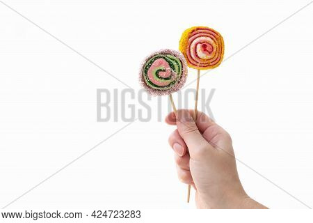 Person Holds Two Colorful Lollypops On Wooden Sticks In Hand On White Background