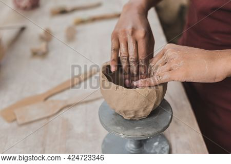 Partial View Of Young African American Woman Sculpting Clay Pot With Hands In Pottery