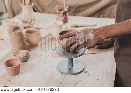 Partial View Of Young African American Man Sculpting Clay Pot With Hand On Table With Equipment In P